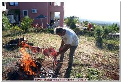 Herr Adonis grillar det grovsaltade lammköttet på kretenskt vis vid sidan av elden!